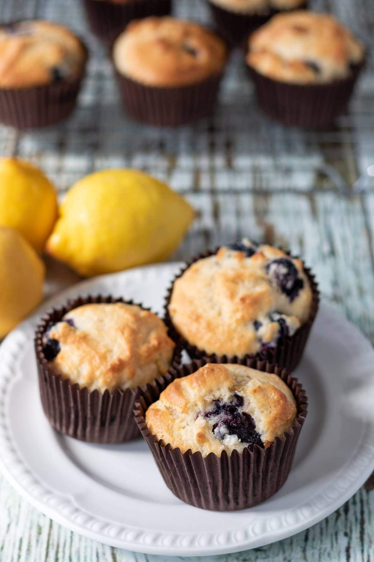 A plate of three lemon blueberry muffins with a wire rack on muffins in the background and lemons in between.