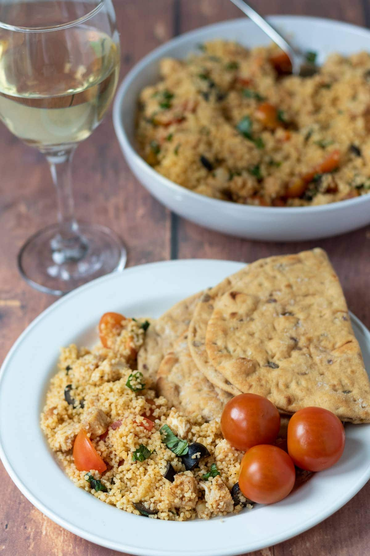 A plate of couscous chicken salad served with cherry tomatoes and flat bread. Serving bowl and glass of wine in the background.