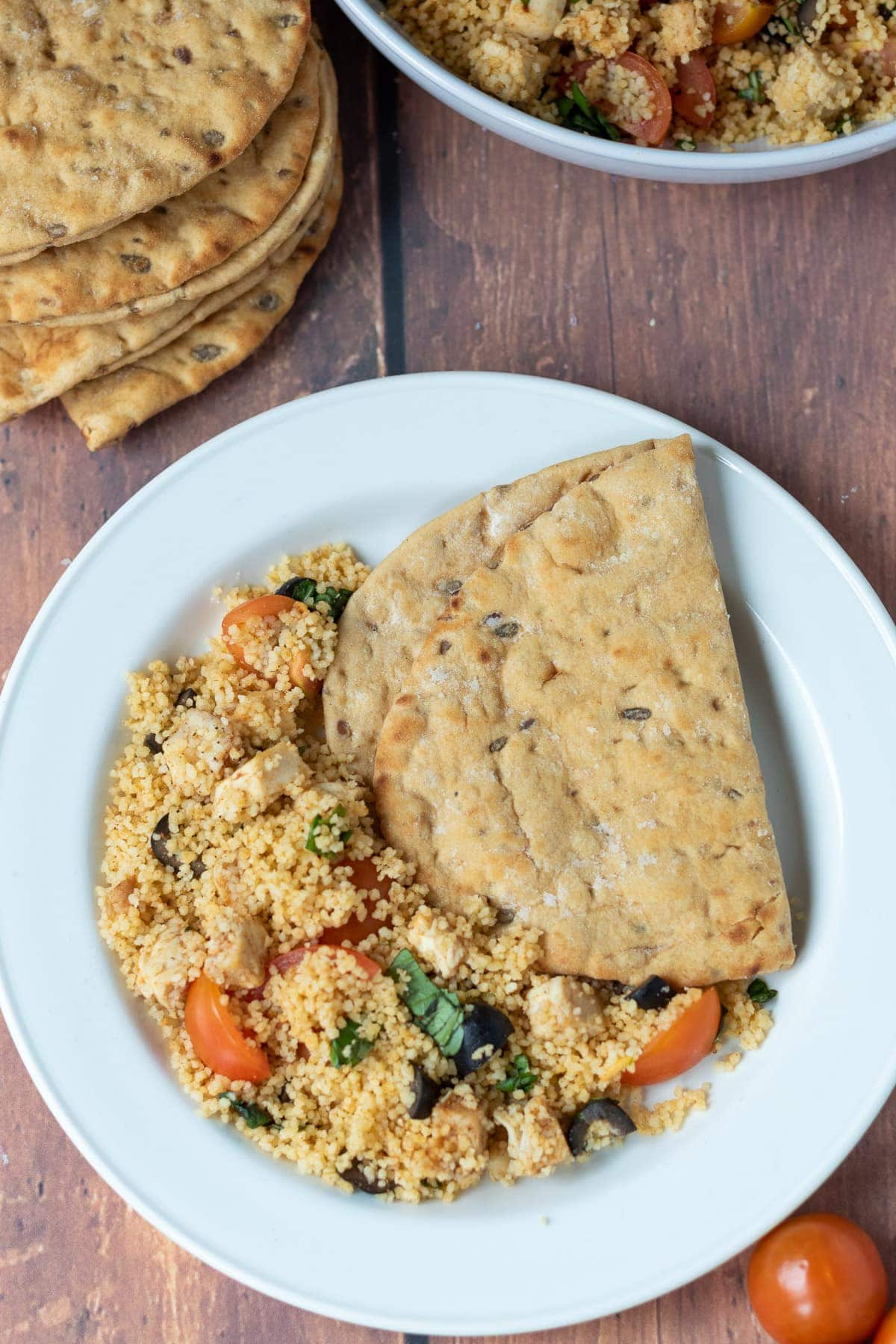 Birds eye view of a plate of chicken couscous salad with flat breads.