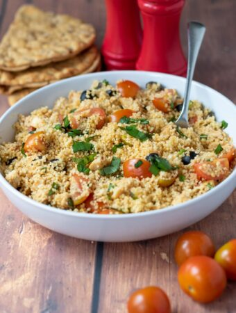 A serving bowl of couscous chicken salad with a spoon in. Cherry tomatoes to the front and salt and pepper shakers and flat bread behind.