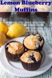 A plate of three lemon blueberry muffins with three lemons to the side. Pin title text overlay at top.