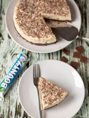 Birds eye view of a slice of no bake bounty coconut cheesecake on a plate with a fork to the side. Rest of the cheesecake at top of picture with a cake slice.
