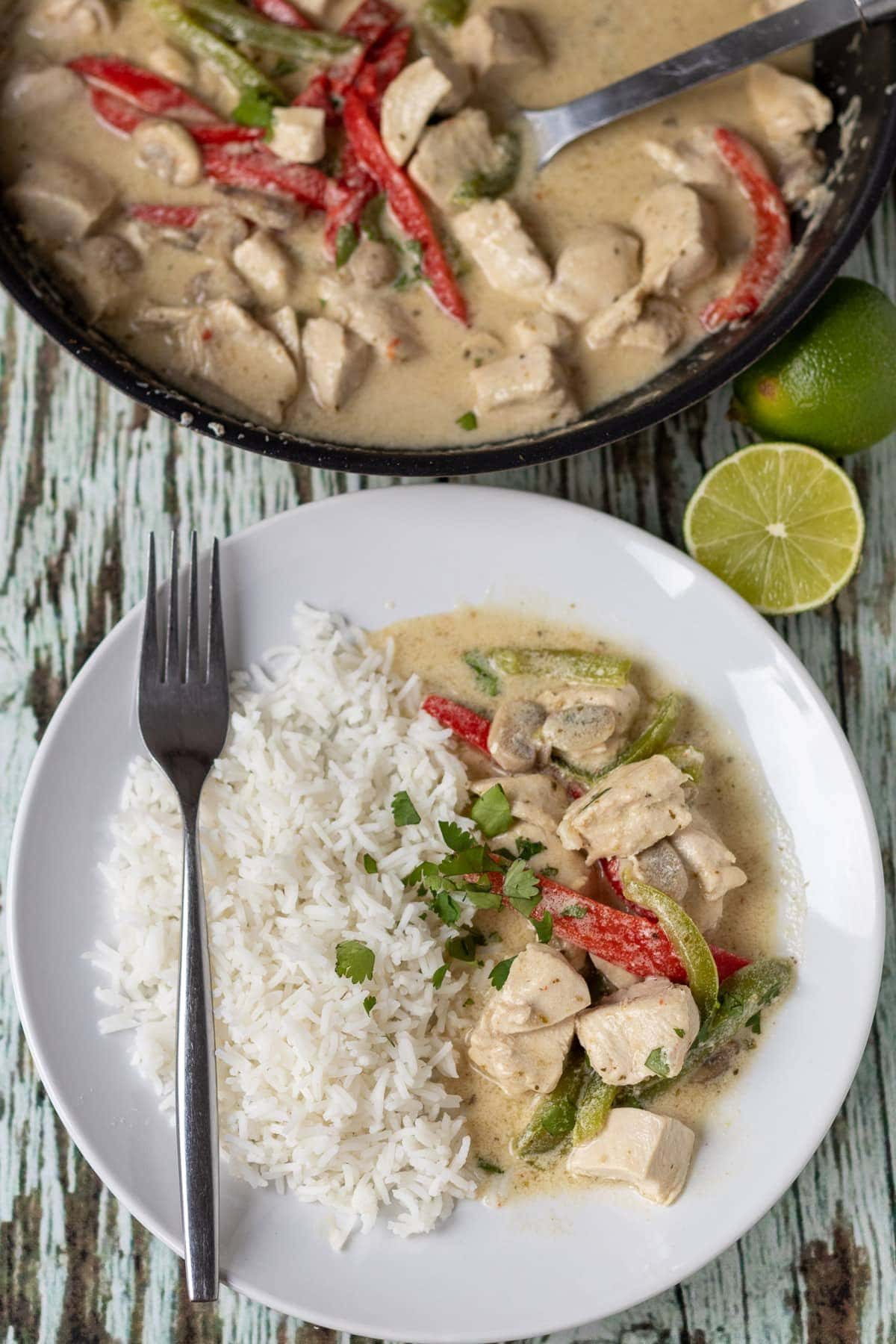 Birds eye view of a plate of Thai chicken curry served with basmati rice at the bottom. Pan of cooked green curry at the top.