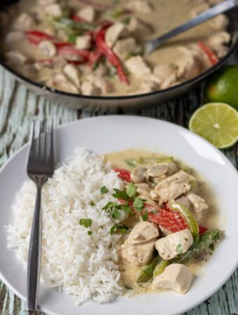 A plate of easy thai green chicken curry served with basmati rice and a fork to the side. Pan of cooked curry in the background.