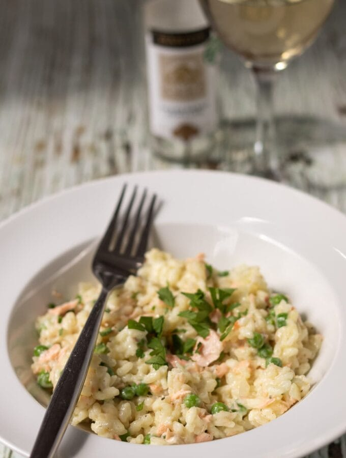 A plate of creamy salmon risotto with peas garnished with chopped parlsey and a fork to the side. A glass of wine and bottle in the background.
