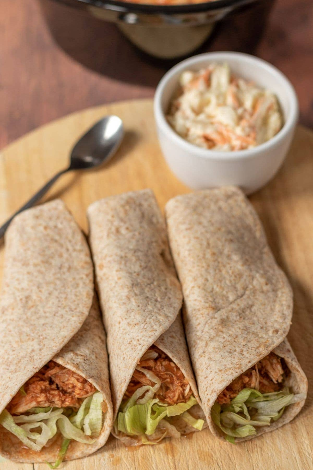 Birds eye view of BBQ chicken wraps on a chopping board. A ramekin of coleslaw and teaspoon above.