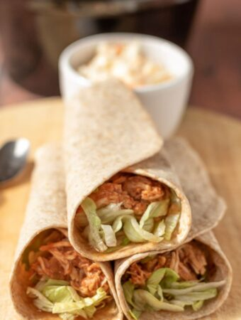 Three rolled slow cooker shredded BBQ chicken wraps stacked with a ramekin of coleslaw in the background.