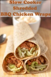 Three stacked slow cooker shredded BBQ chicken wraps on a chopping board with a ramekin of coleslaw in the background. Pin title text overlay at top.